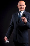 Vieil homme d'affaires avec la carte de crédit et le mobile Images stock
