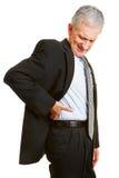 Vieil homme d'affaires ayant des douleurs de dos Photographie stock libre de droits