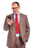 Vieil homme d'affaires de sourire lisant un message ou textoter Photographie stock