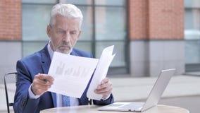 Vieil homme d'affaires Reading Documents, extérieur banque de vidéos