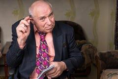 Vieil homme d'affaires Scratching sa tête chauve utilisant le stylo Images libres de droits