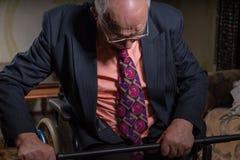 Vieil homme d'affaires songeur Sitting sur son fauteuil roulant Photographie stock libre de droits