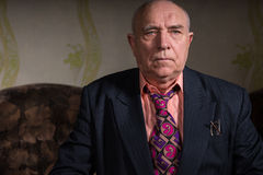 Vieil homme d'affaires strict s'asseyant dans sa chambre Images libres de droits