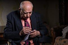 Vieil homme d'affaires sur son écriture de fauteuil roulant sur des notes Photo libre de droits