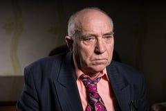 Vieil homme d'affaires triste s'asseyant dans sa chambre Photo libre de droits