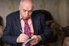 Vieil homme d'affaires triste Writing sur ses petites notes Images stock