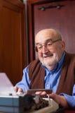 Vieil homme dactylographiant sur une machine à écrire Photo libre de droits
