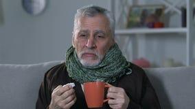 Vieil homme dans l'écharpe buvant du thé chaud et éternuant à la maison, la maladie de grippe, virus banque de vidéos
