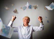 Vieil homme dans le blanc et les euro billets de banque en baisse Image stock