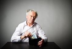 Vieil homme dans le blanc et portefeuille avec l'euro vingt Photographie stock
