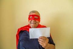 Vieil homme dans le costume de super héros tenant l'enveloppe Photos libres de droits
