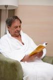 Vieil homme dans le fauteuil affichant un livre Images stock