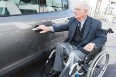 Vieil homme dans le fauteuil roulant à côté de la voiture Photos stock