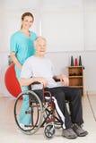 Vieil homme dans le fauteuil roulant avec l'infirmière geriatic Images stock