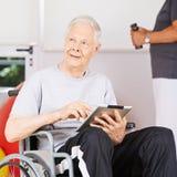 Vieil homme dans le fauteuil roulant avec la tablette Photos stock