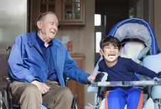 Vieil homme dans le fauteuil roulant avec le garçon handicapé Photographie stock libre de droits