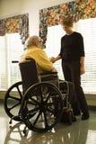 Vieil homme dans le fauteuil roulant et le jeune femme Photos libres de droits
