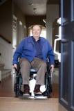 Vieil homme dans le fauteuil roulant à son entrée principale Photo stock