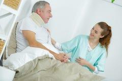 Vieil homme dans le lit avec le bras émouvant d'infirmière photos stock