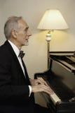 Vieil homme dans le smoking jouant le piano Images stock