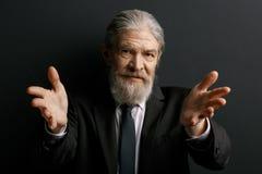 Vieil homme de Beardy dans la veste noire montrant des paumes Images libres de droits