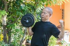 Vieil homme de l'Asie avec des haltères Images stock