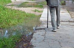 Vieil homme de marche avec un bâton Photos libres de droits