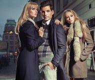 Vieil homme de mode avec la société de deux femmes mignonnes Image stock