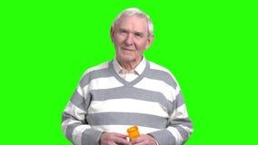 Vieil homme de sourire avec des pilules de boîte banque de vidéos
