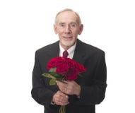 Vieil homme de sourire avec le groupe de roses rouges Images stock