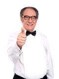 Vieil homme de sourire faisant des gestes des pouces vers le haut Photographie stock