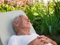 Vieil homme dormant dans le jardin Image stock