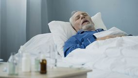 Vieil homme dormant dans le lit à la salle d'hôpital, antibiotiques se tenant sur la table photos libres de droits