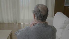 Vieil homme en douleur massant son cou arrière ayant un malaise spinal de crampe ou de colonne de muscle - banque de vidéos