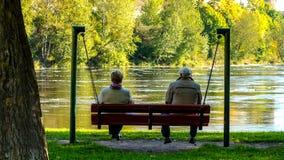 Vieil homme et dame âgée s'asseyant sur les oscillations, Narva, ESTONIE, septembre 2017 images stock