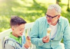 Vieil homme et gar?on mangeant la cr?me glac?e au parc d'?t? photos stock