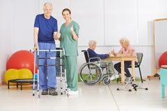 Vieil homme et infirmière gériatrique tenant des pouces  Image libre de droits