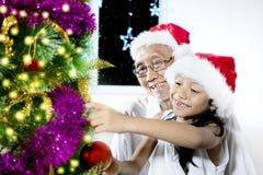 Vieil homme et petite-fille avec l'arbre de Noël Photographie stock