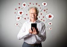 Vieil homme et téléphone intelligent Jour de Valentine Photos stock