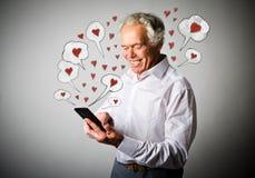 Vieil homme et téléphone intelligent Jour de Valentine Photo libre de droits
