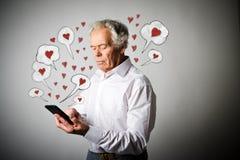 Vieil homme et téléphone intelligent Jour de Valentine Images libres de droits
