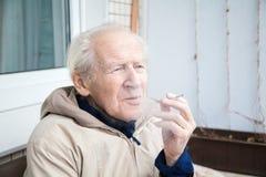 Vieil homme exhalant la fumée Photos stock
