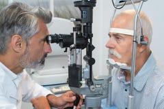 Vieil homme faisant examiner des yeux par l'ophtalmologiste photographie stock libre de droits