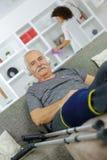 Vieil homme heureux avec des béquilles se reposant sur le sofa Photographie stock libre de droits