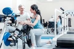 Vieil homme heureux dans le fauteuil roulant et son entraîneur de sourire Image libre de droits
