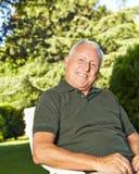 Vieil homme heureux dans un jardin Photographie stock