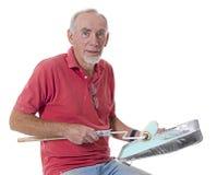 Vieil homme heureux disposant à peindre avec le rouleau Photographie stock libre de droits
