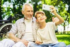 Vieil homme heureux faisant le selfie avec son petit-fils s'asseyant en parc au pique-nique Photo libre de droits