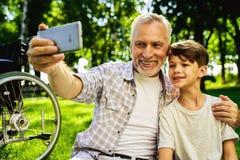 Vieil homme heureux faisant le selfie avec son petit-fils s'asseyant en parc au pique-nique Images libres de droits