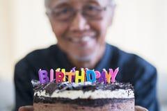 Vieil homme heureux montrant le gâteau d'anniversaire image stock